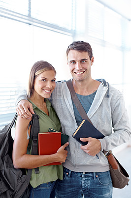 Buy stock photo Young student couple with their arms around each other holding books and smiling at the camera
