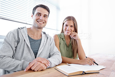 Buy stock photo Two students sitting in front of open books and smiling at the camera