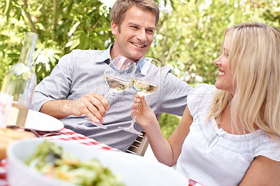 Buy stock photo A mature couple toasting their wine while enjoying a lunch date