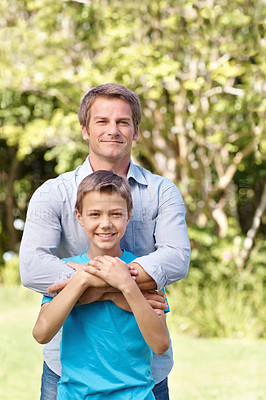 Buy stock photo A loving father embracing his son while standing outdoors on a sunny day