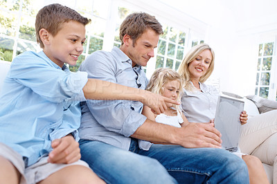 Buy stock photo A young boy pointing at a laptop screen while sitting with his family