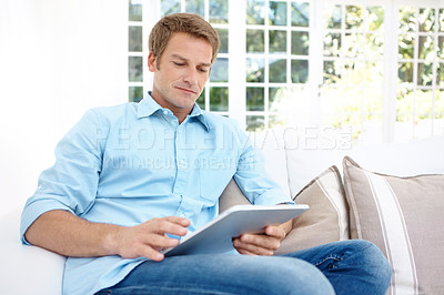 Buy stock photo A handsome mature man using a digital tablet from the comfort of home