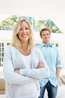 Buy stock photo A pretty woman crossing her arms with her husband standing in the background