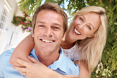Buy stock photo Portrait of happy couple with the woman hugging her partner from behind