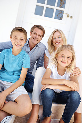 Buy stock photo Portrait of a happy family sitting on the outside step of their house