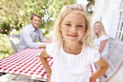 Buy stock photo A pretty blonde girl standing outside while her parents siting in the background