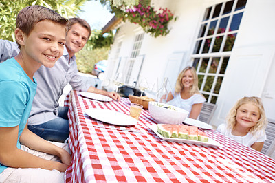Buy stock photo A family sitting outside having a meal and smiling at the camera