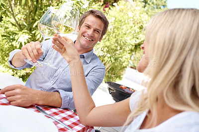 Buy stock photo A smiling couple toasting each other sitting outside drinking wine and eating a meal