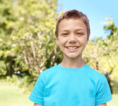 Buy stock photo Portrait of a young smiling boy while he stands outside in the garden with copyspace