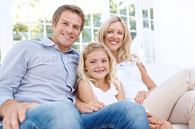 Buy stock photo Portrait of a smiling mother, father and daughter sitting on their couch