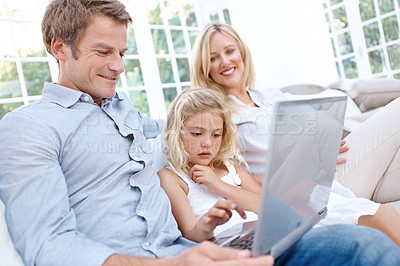 Buy stock photo A happy couple sitting on their couch with their daugher looking at a laptop