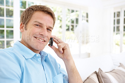 Buy stock photo A man smiling and talking on his cell phone