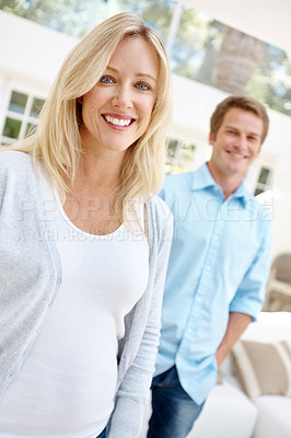 Buy stock photo Portrait of an attractive woman with her husband standing in the background
