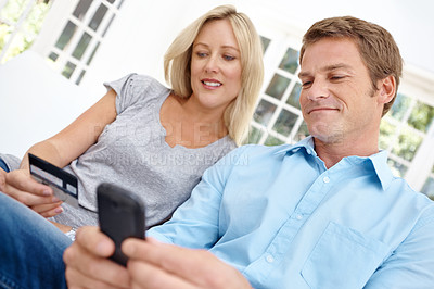 Buy stock photo A man sitting with his wife holding up a cell phone and she is holding his credit card