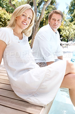 Buy stock photo A smiling couple sitting outside with their feet in the pool