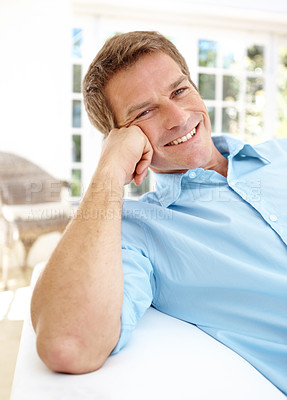 Buy stock photo Handsome mature man smiling while relaxing at home