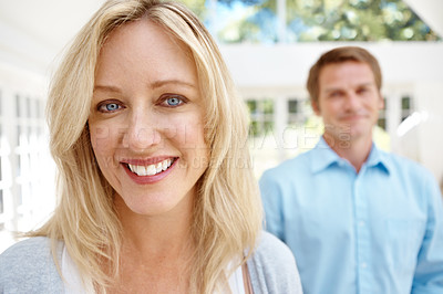 Buy stock photo Beautiful mature woman smiling while her husband standing in the background
