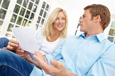 Buy stock photo Attractive mature couple reading through a document together while sitting at home
