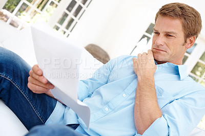 Buy stock photo Handsome mature man reading a document while sitting at home