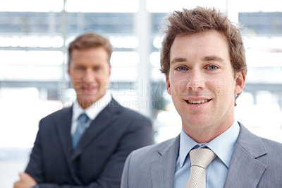Buy stock photo Portrait of a young businessman smiling with a colleague blurred in the background