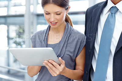 Buy stock photo A beautiful young businesswoman working on her digital tablet while standing next to a colleague