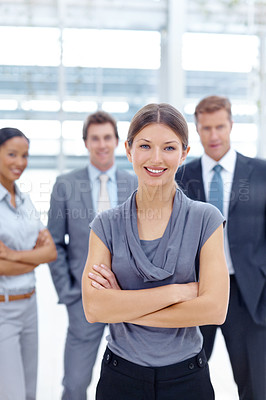 Buy stock photo A young businesswoman standing in front of her team and crossing her arms