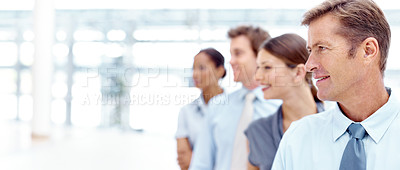 Buy stock photo A team of businesspeople in a line and looking towards copyspace