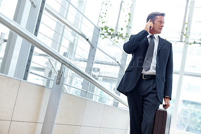 Buy stock photo A handsome businessman walking with his suitcase while talking on the phone