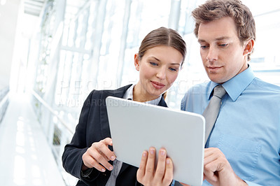 Buy stock photo Two attractive colleagues working together on a digital tablet