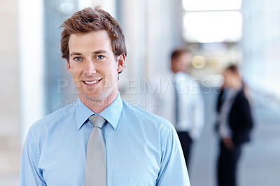 Buy stock photo A handsome young businessman smiling at the camera with his co-workers in the background