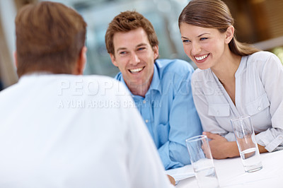 Buy stock photo A happy couple smiling at their financial advisor