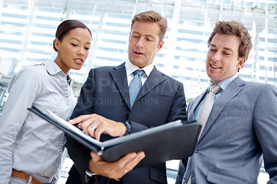 Buy stock photo Group of three businesspeople looking at paperwork together