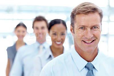 Buy stock photo Mature businessman smiling while his coworkers stand behind him in a row
