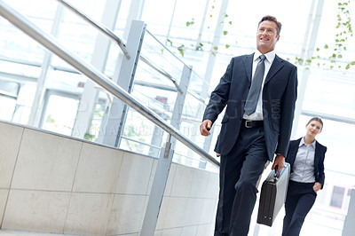Buy stock photo Mature businessman walking along with a female coworker behind him