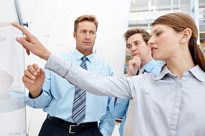 Buy stock photo Young businesswoman pointing at a board while in a meeting with her coworkers