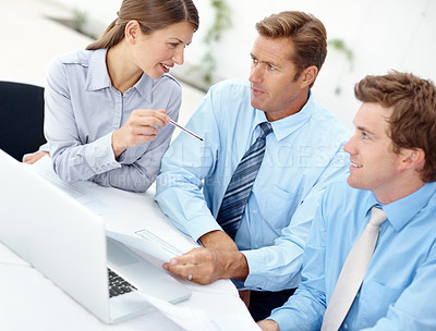 Buy stock photo Group of businesspeople working together while using a laptop