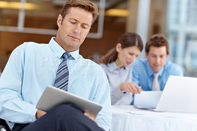 Buy stock photo Businessman using a digital tablet while his colleagues work on a laptop in the background