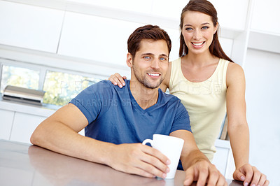 Buy stock photo Boyfriend and girlfriend sitting in their kitchen taking a break with a beverage