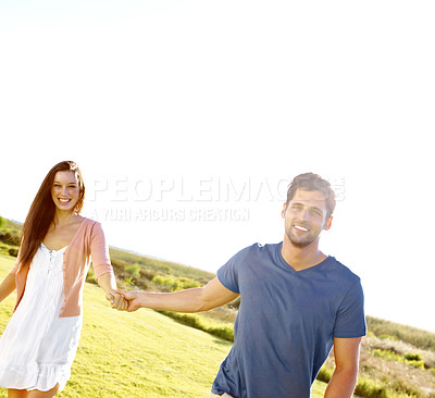 Buy stock photo A happy couple holding hands and running through a field with copyspace