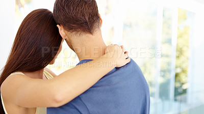 Buy stock photo Rearview shot of a young couple embracing one another and looking through a window