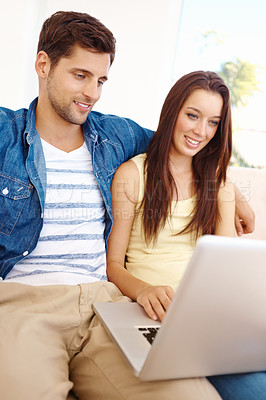 Buy stock photo Shot of a good-looking young couple working on a laptop while sitting on a sofa in their living room