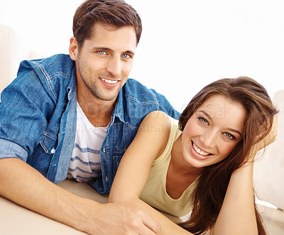 Buy stock photo Low angle portrait of a happy-looking young couple lying on the floor of their lounge