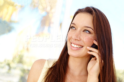 Buy stock photo Close up shot of an attractive young woman talking on a cellphone outside in front of some windows