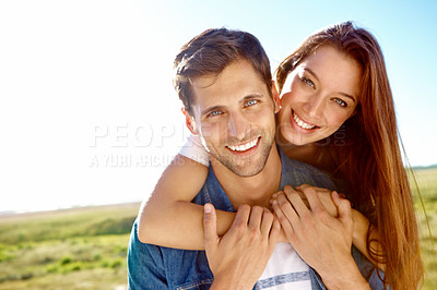Buy stock photo Portrait of a young woman hugging her husband from behind while enjoying a day out