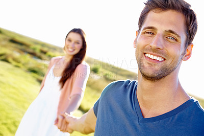 Buy stock photo Close up portrait of a handsome young man leading his girlfriend by the hand through a field