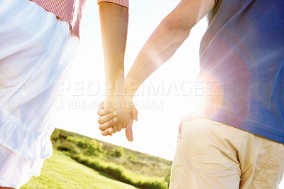 Buy stock photo Cropped close up shot of a young couple holding hands while walking in a field on a sunny day
