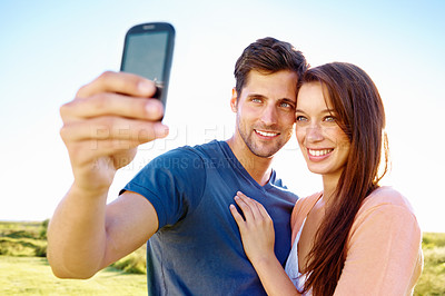 Buy stock photo Shot of a young couple taking a self portrait with a cell phone camera while enjoying a day out