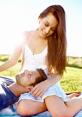 Buy stock photo Shot of a young man lying on his girlfriend's lap while they enjoy the sunshine together
