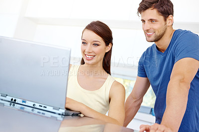 Buy stock photo Cute young couple using a laptop together in the kitchen at home