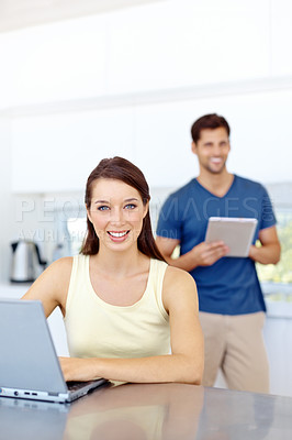 Buy stock photo Young woman using a laptop in her kitchen while her partner uses a tablet in the background